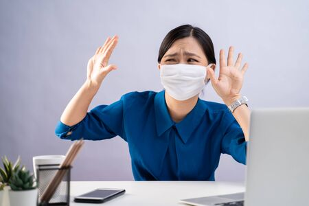 Don't Touch me. Asian woman in blue shirt wearing protective face mask, panic disgusted and showing hand stop sign at office. isolated on white background. Imagens