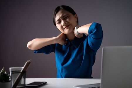 Asian woman in blue shirt working on a laptop was sick with body pain sitting at office. isolated on white background. Low key. Imagens - 150414262