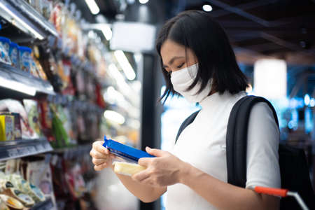 Asian woman wearing protective face mask prevention virus and pollution at department store, Shopping buying foods at supermarket. New lifestyle with Corona Virus COVID-19. Imagens - 150874768