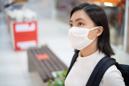 Asian woman wearing protective face mask prevention virus and pollution, coughing and standing at department store. New lifestyle with Corona Virus COVID-19. Imagens - 150874770
