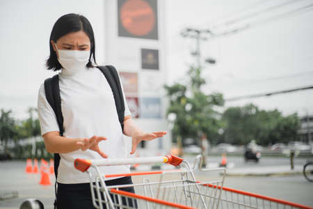 Asian woman wearing protective face mask prevention virus and pollution, coughing and standing at department store. New lifestyle with Corona Virus COVID-19. Stock Photo