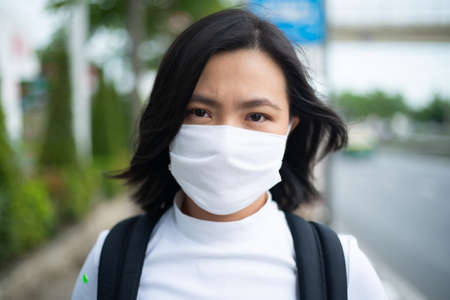 Asian woman wearing protective face mask prevention virus and pollution, coughing and standing at department store. New lifestyle with Corona Virus COVID-19. Imagens - 150874769