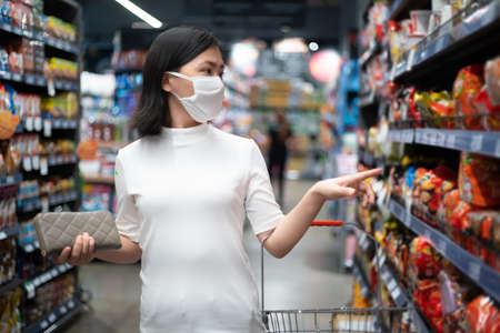 Asian woman wearing protective face mask prevention virus and pollution, coughing and standing at department store. New lifestyle with Corona Virus COVID-19. Imagens - 150874771