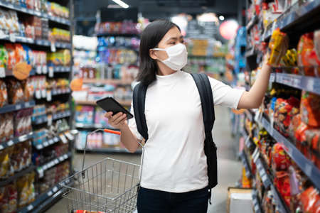 Asian woman wearing protective face mask prevention virus and pollution at department store, Shopping buying foods at supermarket. New lifestyle with Corona Virus COVID-19.