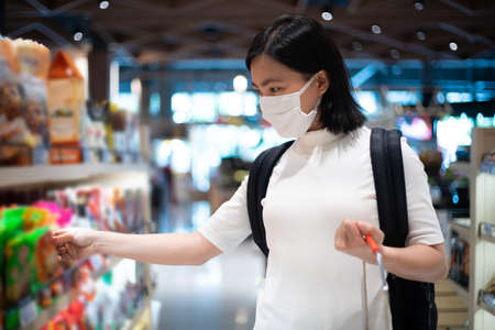 Asian woman wearing protective face mask prevention virus and pollution, coughing and standing at department store. New lifestyle with Corona Virus COVID-19. Imagens