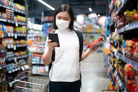 Asian woman happy smiling wearing protective face mask prevention virus and pollution, walking to department store for shopping. New lifestyle with Corona Virus COVID-19. Imagens