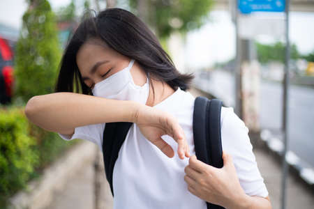 Asian woman wearing protective face mask prevention virus and pollution, coughing and standing at department store. New lifestyle with Corona Virus COVID-19. Imagens - 150874781
