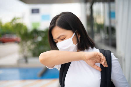 Asian woman happy smiling wearing protective face mask prevention virus and pollution, walking to department store for shopping. New lifestyle with Corona Virus COVID-19. Imagens - 150874891