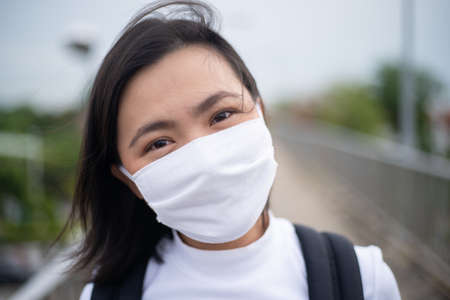 Asian woman happy smiling wearing protective face mask prevention virus and pollution, walking to department store for shopping. New lifestyle with Corona Virus COVID-19. Reklamní fotografie