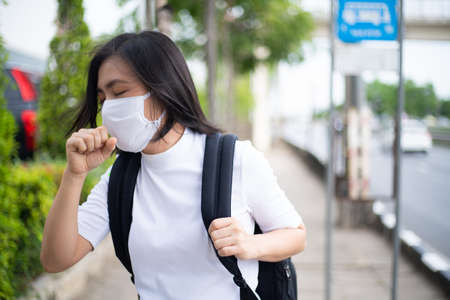 Asian woman wearing protective face mask prevention virus and pollution, coughing and standing at department store. New lifestyle with Corona Virus COVID-19. Imagens - 150874898