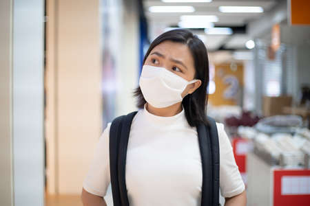 Asian woman happy smiling wearing protective face mask prevention virus and pollution, walking to department store for shopping. New lifestyle with Corona Virus COVID-19. Imagens - 150874904