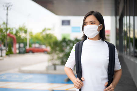 Asian woman happy smiling wearing protective face mask prevention virus and pollution, walking to department store for shopping. New lifestyle with Corona Virus COVID-19. Imagens - 150874905