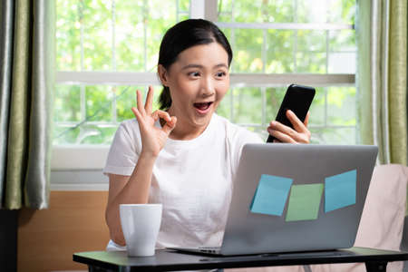 Asian woman happy video call with laptop holding smart phone sitting on the bed and showing OK sign at home. WFH. Work from home. Social distancing concept. Imagens - 152745920