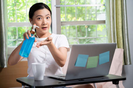 Asian woman washing hands using hand sanitizer gel before working with laptop sitting on the bed at home. WFH. Work from home. Social distancing concept.