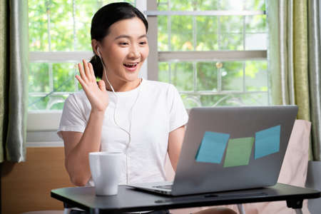 Asian woman with earphone happy meeting by video call with laptop sitting on the bed at home. WFH. Work from home. Social distancing concept.