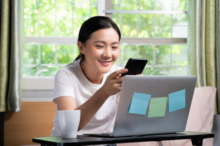 Asian woman happy typing message with smart phone sitting on the bed at home. WFH. Work from home. Social distancing concept. Imagens - 152745931