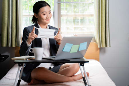 Asian woman happy wearing protective face mask meeting by video call with laptop sitting on the bed at home. WFH. Work from home. Social distancing concept. Imagens - 152745928