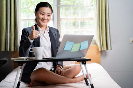 Asian woman happy video call with laptop sitting on the bed and showing OK sign at home. WFH. Work from home. Social distancing concept. Imagens - 152745934