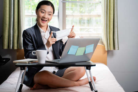 Asian woman happy video call with laptop sitting on the bed and showing OK sign at home. WFH. Work from home. Social distancing concept. Imagens - 152745935
