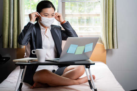 Asian woman happy video call with laptop sitting on the bed and showing OK sign at home. WFH. Work from home. Social distancing concept. Imagens
