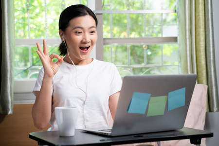 Asian woman happy video call with laptop sitting on the bed and showing OK sign at home. WFH. Work from home. Social distancing concept. Imagens - 152745938