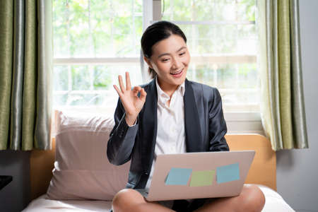 Asian woman happy video call with laptop sitting on the bed and showing OK sign at home. WFH. Work from home. Social distancing concept. Imagens - 152745949