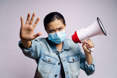 Asian woman wearing protective face mask shouting with megaphone isolated on white background. 免版税图像