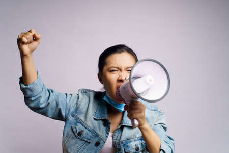 Asian woman wearing protective face mask shouting with megaphone isolated on white background.