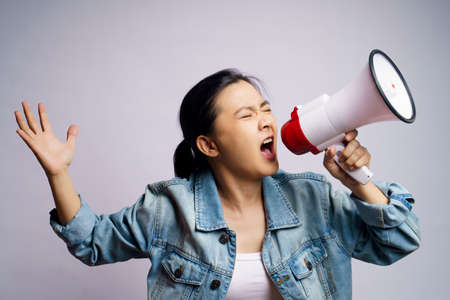 Asian woman shouting with megaphone isolated on white background.