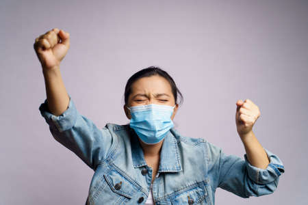 Asian woman wearing protective face mask shouting isolated on white background.