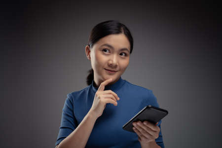 Asian woman happy typing on smart phone isolated on background.