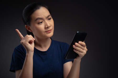 Asian woman looking at smart phone reading news and feel confused.