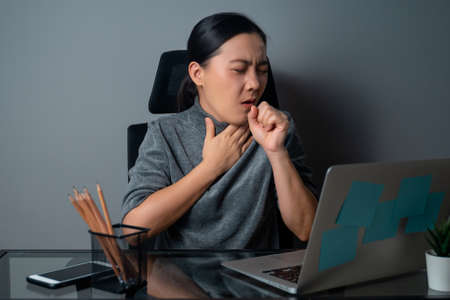 Asian woman working on a laptop was sick with stomach ache sitting at office. isolated on gray background.