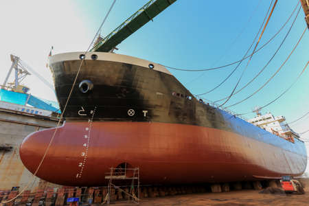 Oil tanker vessel black color on top and red color down below on dry dock to do repair