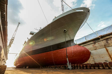 Gray color navy ship on dry dock for maintenance and repair