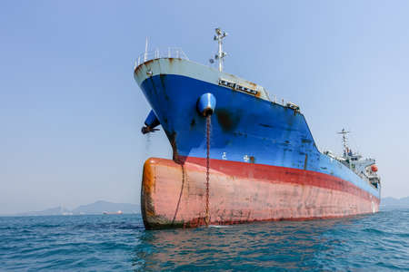 Cargo oil tanker blue and red color drop anchor one side Stock Photo