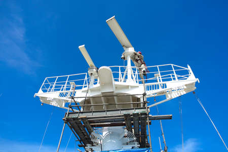 Radar antenna of commercial vessel repairing by one man climb on top of antenna and below had erect scaffolding for protection. Zdjęcie Seryjne