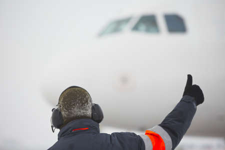 Member of ground crew is showing OK sign to pilot  Stock Photo