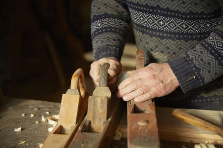 Old cabinet-maker is working with wooden planers in his workshop. photo