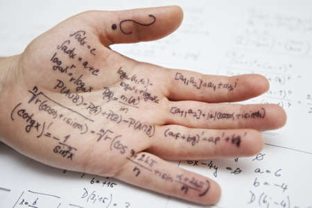 described: Hand of student with cheat sheet for math exam Stock Photo