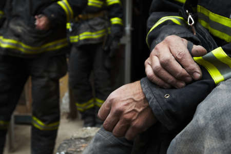 protective work wear: Sadness and hope. Firefighter resting during the rescue work.  Stock Photo
