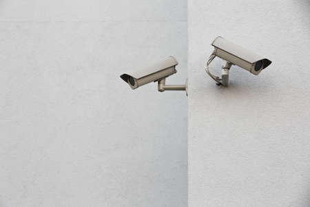 Two security cameras on a wall.  photo