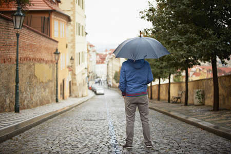 Rainy day in Prague - young man with umbrella  Stock Photo