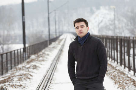 Young man on railroad track in winter photo