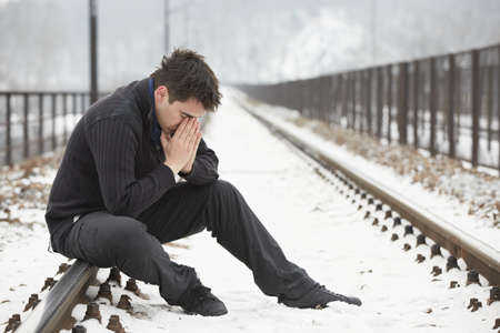 economic depression: Sad man in railroad track