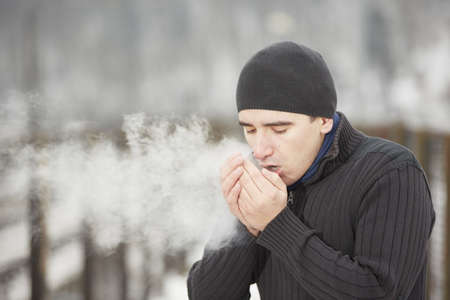 Young man in winter landscape and warmed the hands of breath Stock Photo
