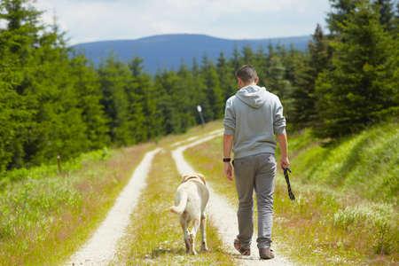 séta: Fiatal ember a kutyájával Stock fotó