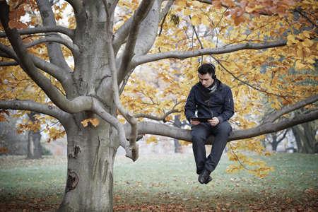 escuchando musica: Hombre joven en parque del otoño Foto de archivo