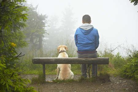Homme perdu avec son chien en montagne
