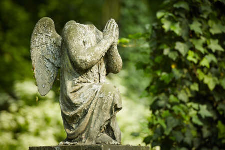 horrific: Cherub without head  Damaged statue on old cemetery  Stock Photo